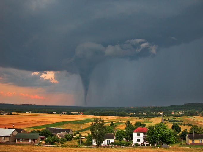 View of the serene countryside and stormy sky with a tornado in the background.